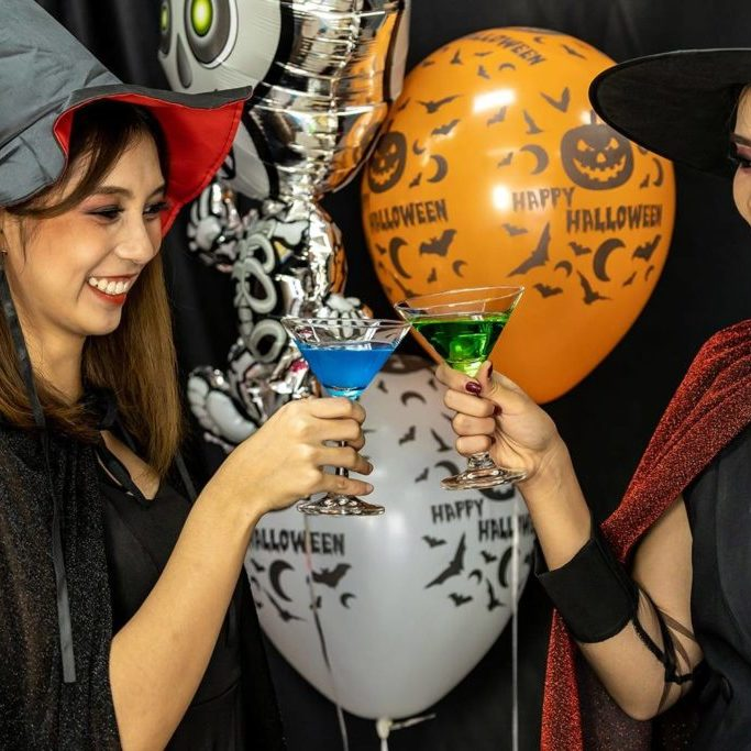 Group of young adult and teenager people celebrating a Halloween party carnival Festival in Halloween costumes drinking alcohol cocktail
