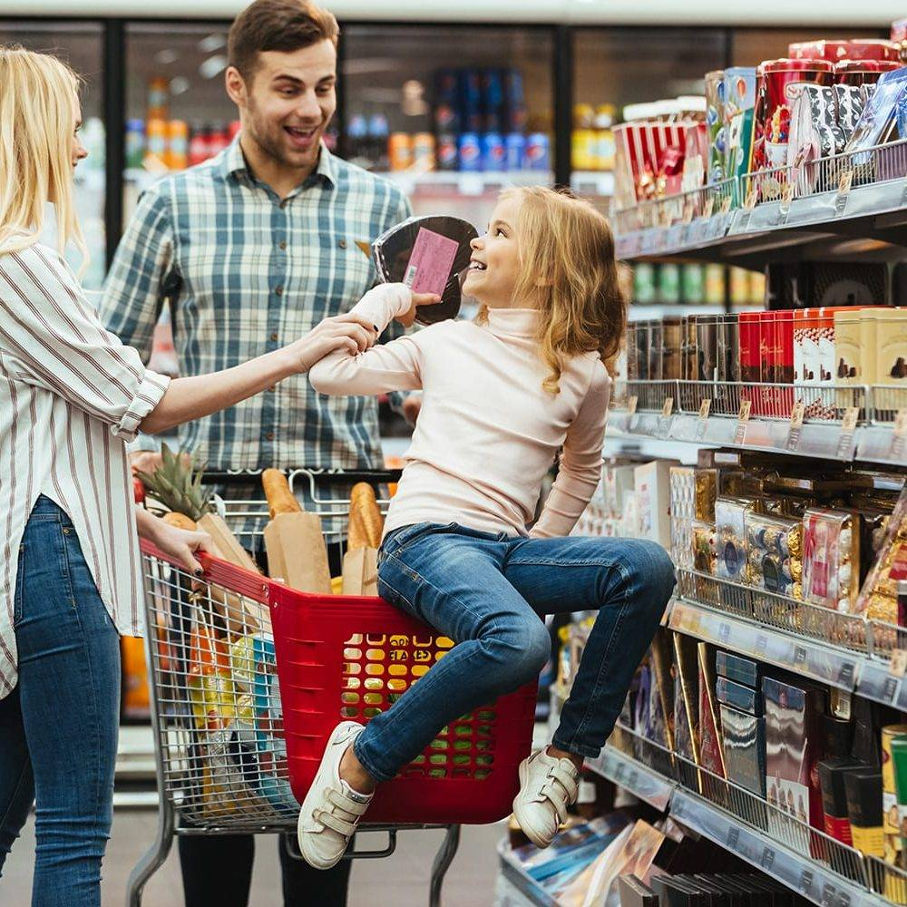Joyful little girl sitting on a shopping cart and choosing candy with her parents at the supermarket