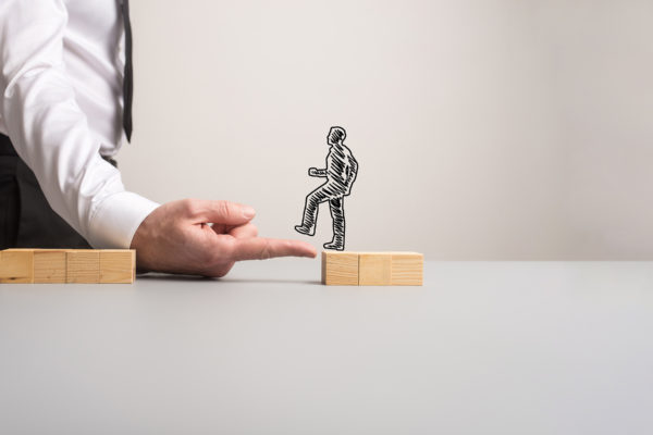 Businessman making a bridge of his finger for a silhouetted businessman to walk across one pile of wooden blocks to the other in a conceptual image. With copy space.
