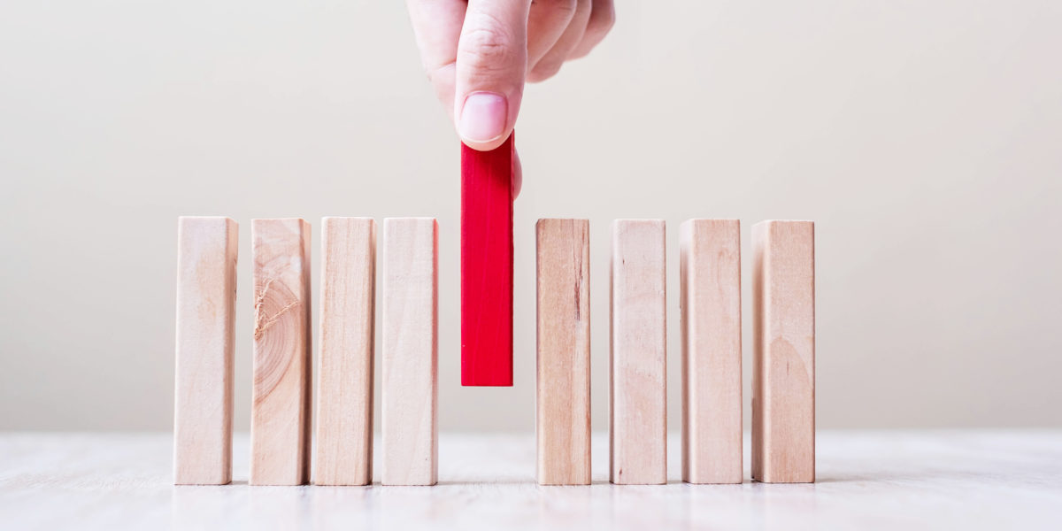 Businessman hand placing or pulling Red wooden block on table. Business planning, Risk Management, Solution, leader, strategy, different and Unique Concepts